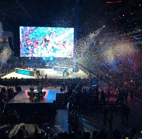 Esports stadium with a victory screen and lots of confetti raining down upon the competitors as the winning team is awarded